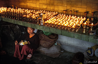 Photo: Tibetan Buddhist monk eats is one meal of the day in a candle lit room generally used for prayer and meditation.  India, West Bengal, Darjeeling Area