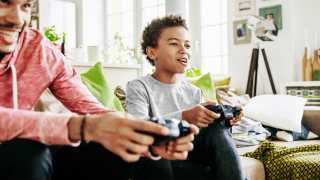 man and young boy play video game
