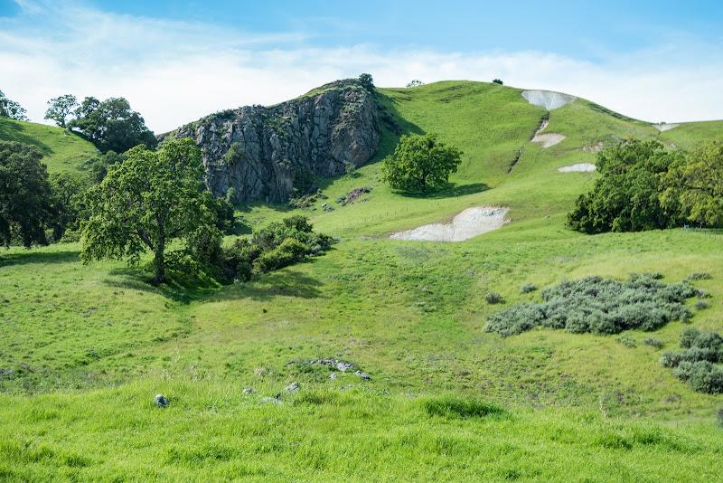 Beautiful rocks behind rising grassland
