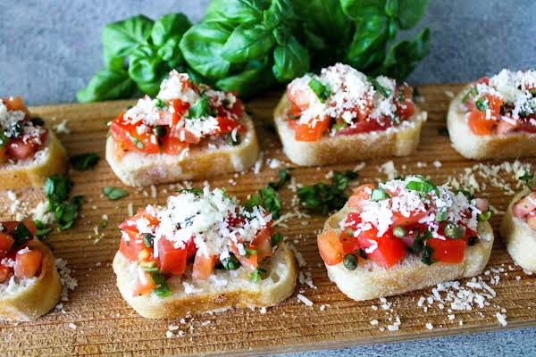 A Tray Of Bruschetta Sprinkled With Parmesan Cheese.