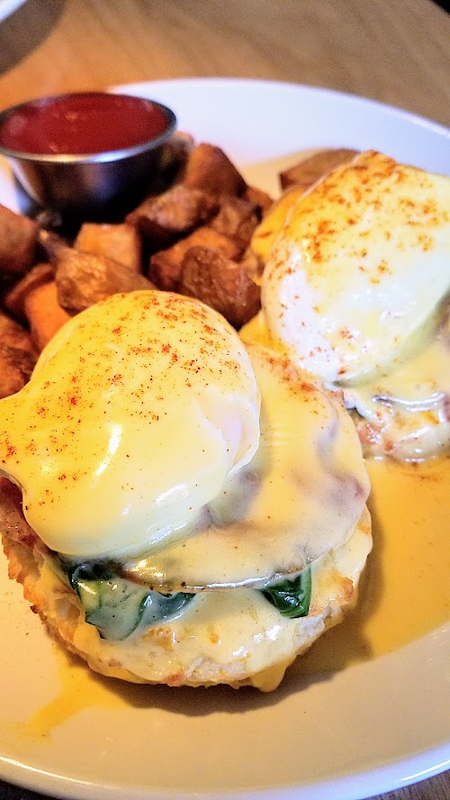 Circa 33 brunch dish of Circa Benedict with housemade biscuit, coppa, poached eggs, béarnaise, house potatoes