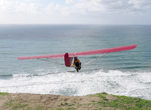 Photo: The Red Goat launches over winter surf. The wind is light, judging from the lack of white caps on the ocean, and from the loss of altitude on take off. The ailerons and rudder are being used together to command a left turn. The elevator is in neutral position, indicating proper balance for this airspeed. Since the pilot has nothing to do with his left hand, he might be holding a cup of coffee, or just grasping the strut as shown here. Torrey Pines Gliderport, February 2010, Floyd Fronius is flying,