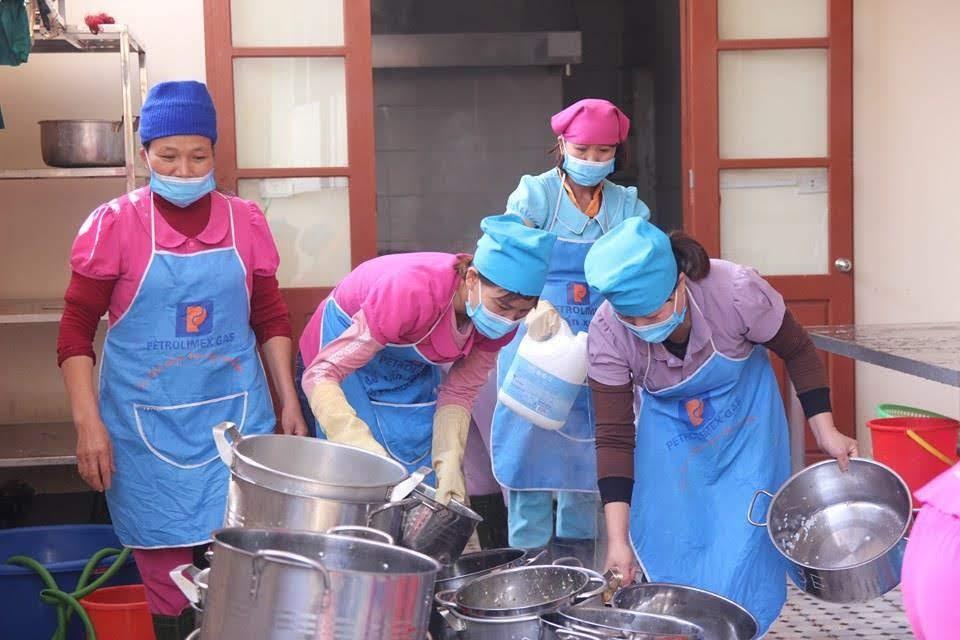 Nhân viên nhà bếp (bán trú) đeo khẩu trang vệ sinh xoong chảo trước và sau khi chế biến thức ăn