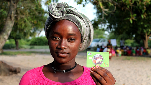 A social grant recipient shows off her payments card.