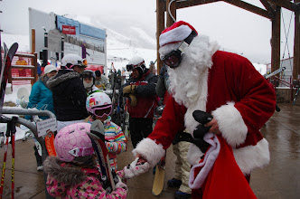 """Photo: Two young guests on Santa's """"Nice"""" list score candy canes in the plaza."""