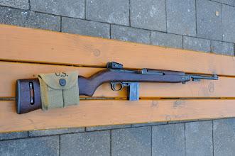 Photo: Americká poloautomatická puška M1 Carbine. Lehká puška spíše pistolové ráže používaná převážně u pilotů letadel, tankistů, ale i pěchoty. Byla všude, kde byla potřeba krátká, lehká a spolehlivá puška. Náboj měl díky menším rozměrům a hmotnosti menší ranivý účinek, a proto někdy nepřítel padl, až na druhou nebo třetí ránu, tedy v případě, že nedošlo k zásahu do hlavy nebo jiné vitální zóny. Zbraň se používala od poloviny 2. světové války, dále našla také uplatnění ve válce v Koreji (1950-1953) a ve Vietnamu (1964-1975). Dodnes je kvůli své přesnosti a snadné obsluze oblíbená u sportovních střelců. Zbraň měla odnímatelný zásobník na 15, později dokonce na 30 ran. Na pažbě můžete vidět sumku na dva zásobníky se značkou U.S.  Autor popisku: Štěpán Pravda, student 1. A.