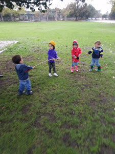 Four preschoolers playing with sticks
