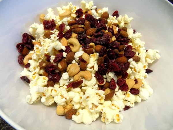 Stir nuts and currants/cranberries into popcorn. Bring sugar, maple syrup, and remaining ingredients to...