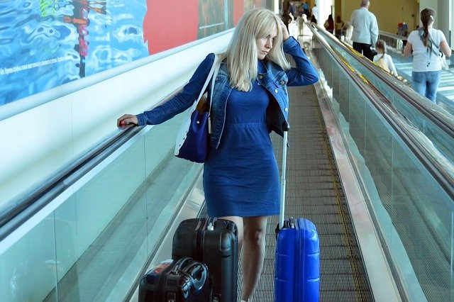 Traveler with anxiety riding on escalator at the airport with her luggage