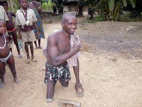Photo: se dirige lestement vers sa maison, en appui sur des morceaux de bois et ses genoux