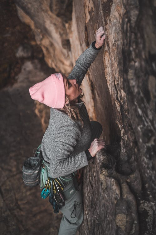 Focused young sportswoman climbing huge cliff in ravine