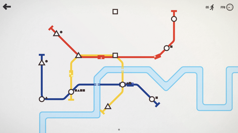 The image shows a screenshot of Mini Metro gameplay. A red, yellow, and blue line connect a variety of triangles, circles, and squares in a simulated city map showing white land and a blue river. The lines intersect at some of the shapes. Each line has a rectangular train traveling along it, holding smaller shapes. Photo credit, wiki images