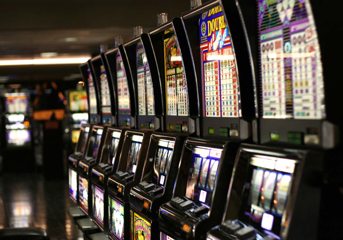 Seven empty slot machines are lined-up next to each other