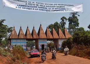 Photo: Eingangstor zum Palastbereich der Chefferie (Königreich) Baleng.  Das Banner verkündet die Totengedenkfeier (frz. lamentations, engl. cry-die od. chop-die) für den im Alter von 86 Jahren verstorbenen Fotso Victor, einen der reichsten Männer Kameruns.