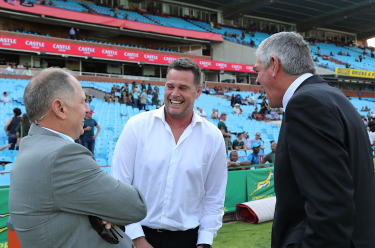 The Springboks coach and SA Rugby head of rugby Rassie Erasmus (C) in good spirits as he chats with TV commentators and analysts Naas Botha (L) and Nick Mallett (R) during the Rugby Championship match between South Africa and New Zealand at Loftus Stadium in Pretoria on October 6 2018.