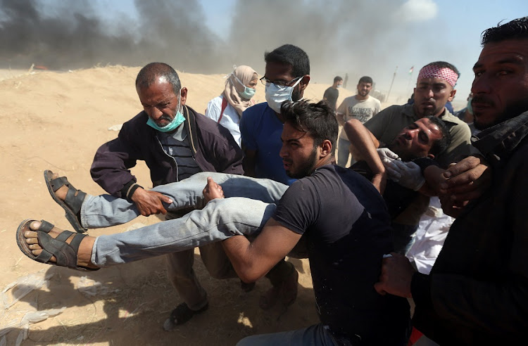 A wounded Palestinian demonstrator is evacuated during a protest marking the 70th anniversary of Nakba, at the Israel-Gaza border in the southern Gaza Strip on Tuesday. Picture: REUTERS/Ibraheem Abu Mustafa