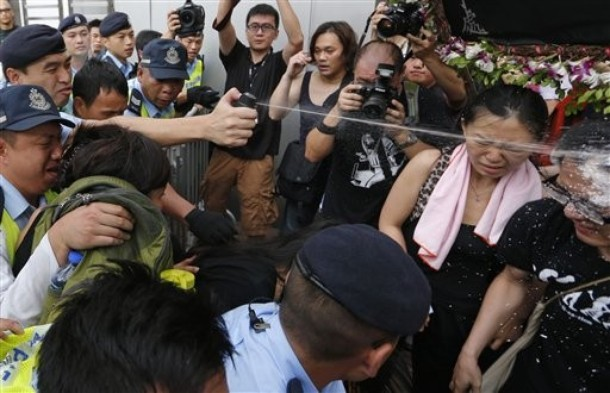 Photo: A police officer release pepper spray to protesters during a gathering near Chinese central government's liaison in Hong Kong to mourn Chinese labor activist Li Wangyang's death in Sunday, June 10, 2012. Li imprisoned for two decades died in a hospital Wednesday one year after being released from jail, and a relative raised doubt on the official explanation that he had hanged himself. Li had advocated for independent labor unions in central China's Hunan province and was caught in the sweeping nationwide crackdown on all forms of dissent after the Tiananmen Square democracy protests were quashed in 1989. (AP Photo/Vincent Yu)