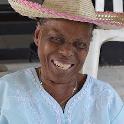 Una mujer afro mayor, que viste sombrero típico y blusa bordada, sonríe con ganas a la cámara, desde el costado noroccidental del Hogar Mónica.