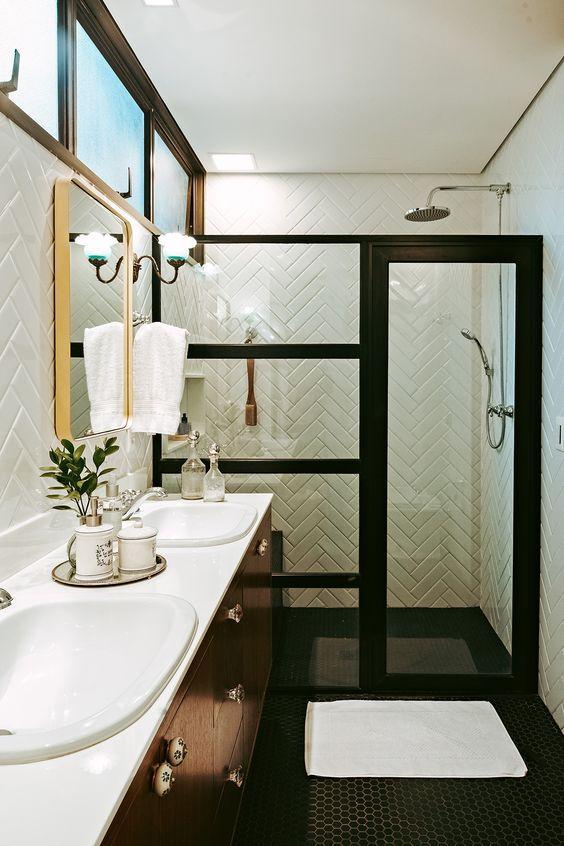 Banheiro com piso hexagonal em formato pequenos preto, box de vidro com moldura e detalhes pretos, azulejo em zig zag branco, armário amadeirado com bancada da pia branca.