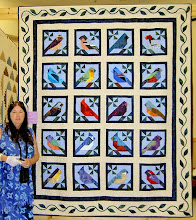 "Photo: Mary with ""A Bird of a Feather"" Quilt. The cardinal was taken from the front cover of ""Quilter's Magazine"" Spring 2000.With the help of the internet we designed the remainder blocks ourselves researching different birds and their colours. All the blocks are paper pieced. The border is machine appliqued with long arm quilting by Donna Moore, Ajax, Ontario"