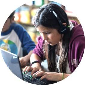 Girl using accessibility features in Chromebook with headphones.