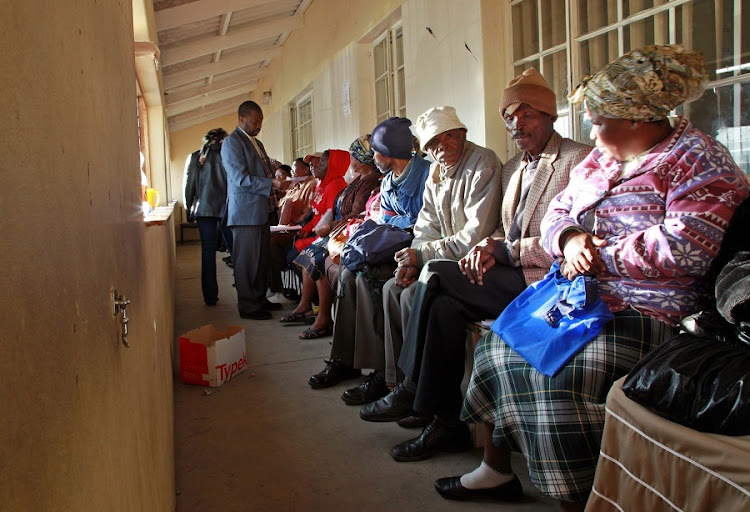 Grant recipients wait for payouts at a South African Social Security Agency office. Picture: SUNDAY TIMES
