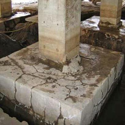 Bloco de fundação de concreto ao qual liga-se um pilar, altamente fissurado sem direção definida.