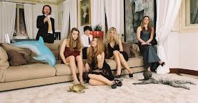 familie zittend op en staand naast een zeer brede bank in woonkamer