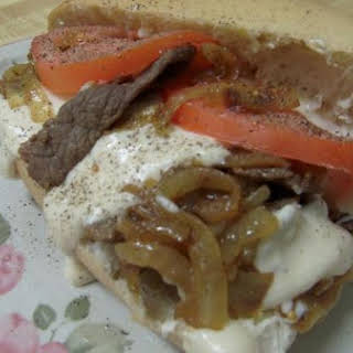 Philly Cheese Steak Sandwiches Smothered With Spicy Cheese Sauce.