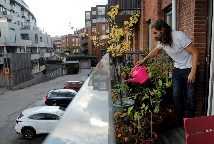 Daniel Jager waters plants on his balcony in Stockholm, Sweden. Picture: REUTERS/Maxim Shemetov