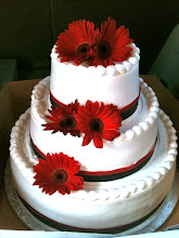 Photo: Italian Wedding Cake: 3-tiers iced in white, Italian whipped cream. Decor: smooth sides with top frosting border and double ribbon wrap in red and black glittered ribbons, finished with fresh red Gerbera flowers.