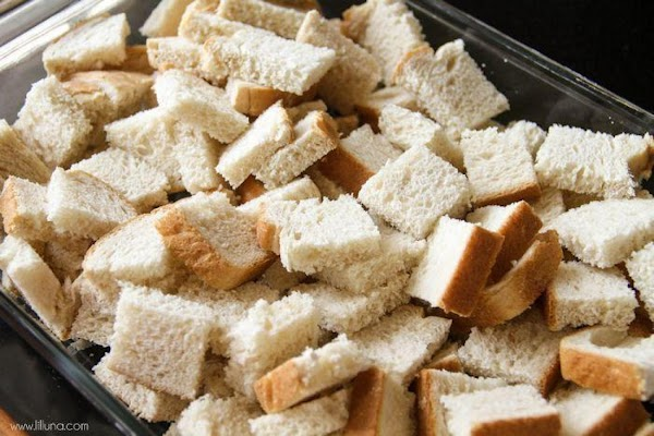Cut bread into 1½ inch squares. Place in a greased 9x13 pan.