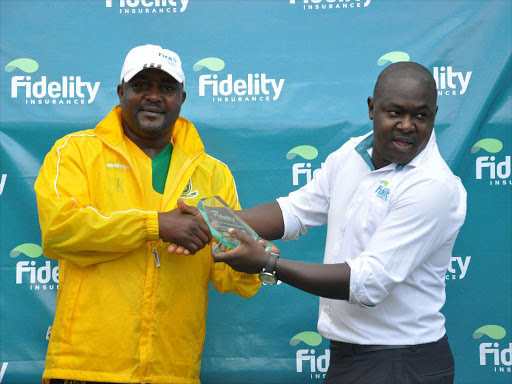 Mathare United Coach Francis Kimanzi receives Coach of the Month Award from Fidelity Insurance Marketing and Business development Manager Nicholas Malesi