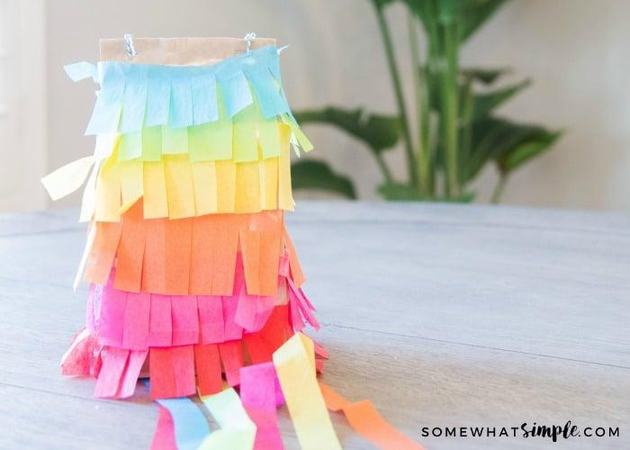 a paper bag pinata made with blue, green, yellow, orange, purple and red paper