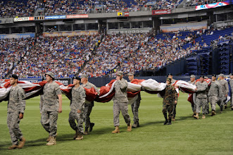 "Photo: Airmen and Soldiers of the Minnesota National Guard carry a large American flag used for the national anthem on the field The Minnesota Twins host the 7th Annual Armed Services Appreciation Day on July 5, 2009 at the Metrodome in Minneapolis , Minnesota. The pregame festivities included Freedom Flight and Liberty Belle hot air balloons, a performance by the United States Air Force Heartland of America Band ""Night Wing and ceremonial first pitches by veterans from conflict s dating bat to World War II. During the game the Twins wore caps honoring the five branches of the Armed Services. All current and former members of the Armed Services and their families received four complimentary tickets to the game.