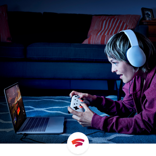 A person plays a game using the Stadia Controller and a laptop.