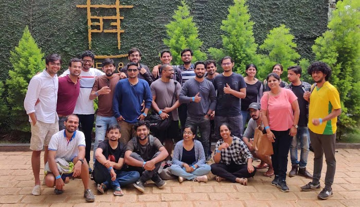 Group photo of the Gameberry Lab team; ~20 men and women in casual clothing facing the camera in an outdoor courtyard