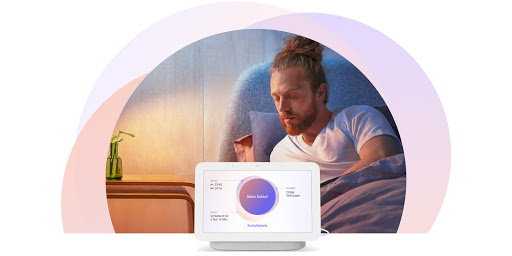 Mann, der aufrecht im Bett sitzt und sich zu seinem Nest Hub-Display neben seinem Bett dreht. Auf dem Display sind personalisierte Schlafinfos zu sehen.