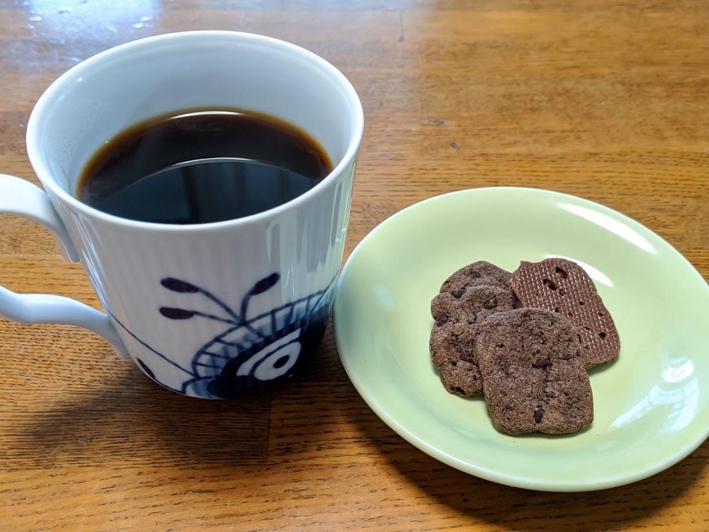 左にコーヒーカップに入ったホットコーヒーと右に小皿に出したカントリーマアムチップスの画像