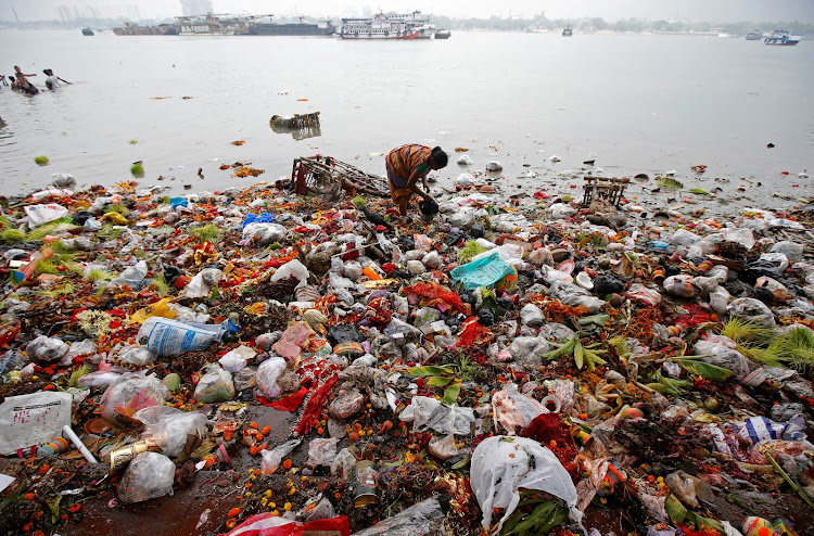A woman collects items thrown by devotees as religious offerings in the Ganges river, after the celebrations of the last day of Navratri festival, in Kolkata, India.