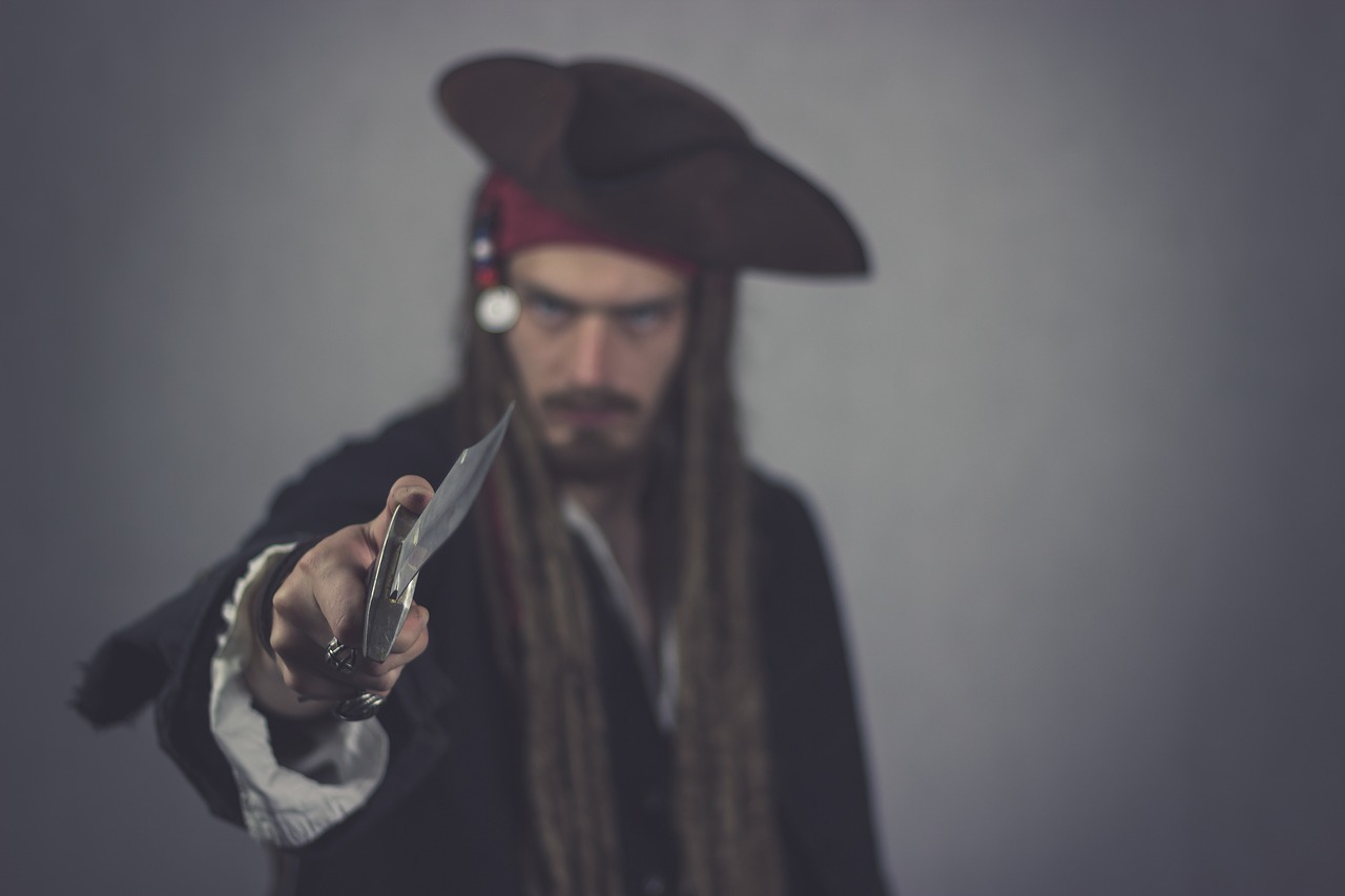 Man in pirate dress brandishing a sword at the reader
