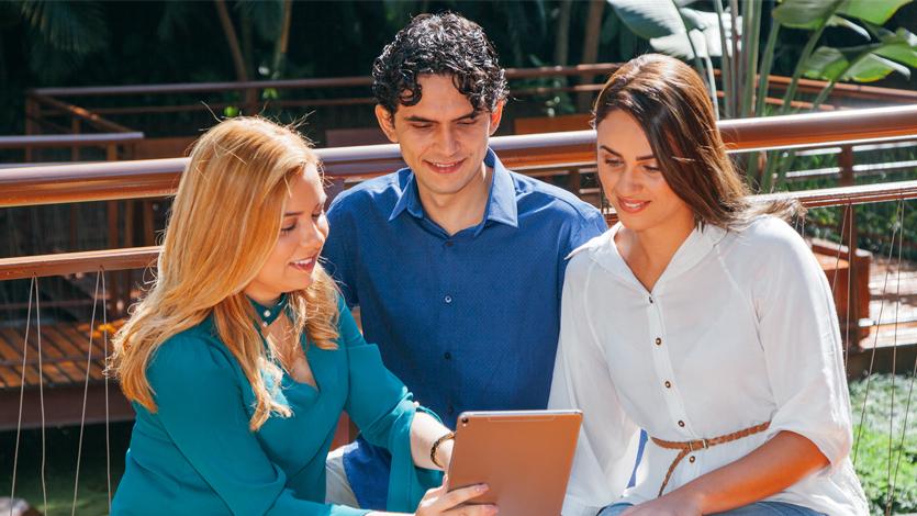 Homem e duas mulheres em reunião informal, sentados em um banco coletivo, observando um tablet.