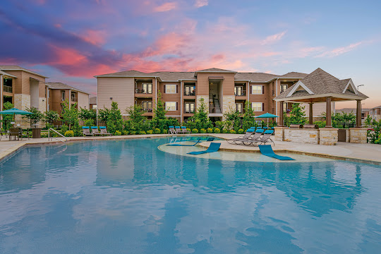 Resort-style pool and apartment buildings at dusk with beautiful landscaping