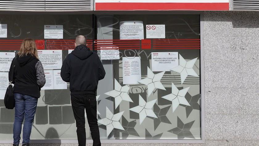 Una pareja frente a una oficina de la Seguridad Social.