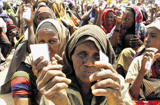 Displaced women wait to receive non-food items from the UN High Commissioner for Refugees at the Maajo settlement. File photo.