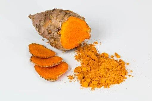 A bright yellow turmeric in powder form and dried turmeric root