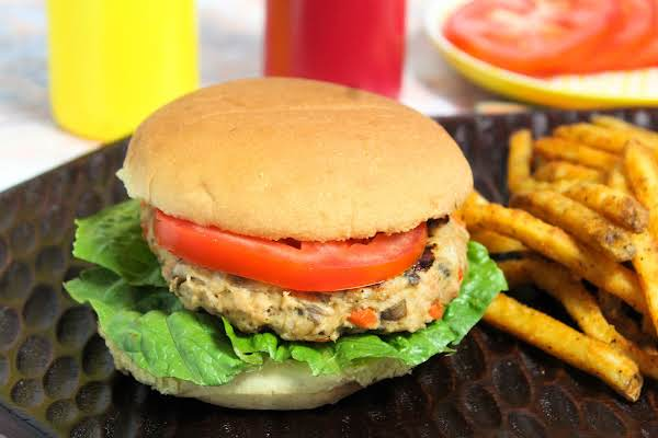 Grilled Chicken Patty On A Roll With Lettuce And Tomato.