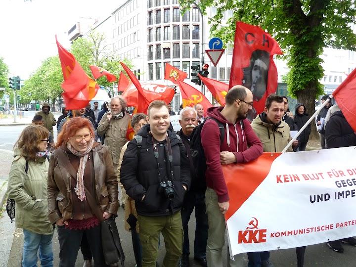Demonstrierende mit roten Fahnen und Transparent.