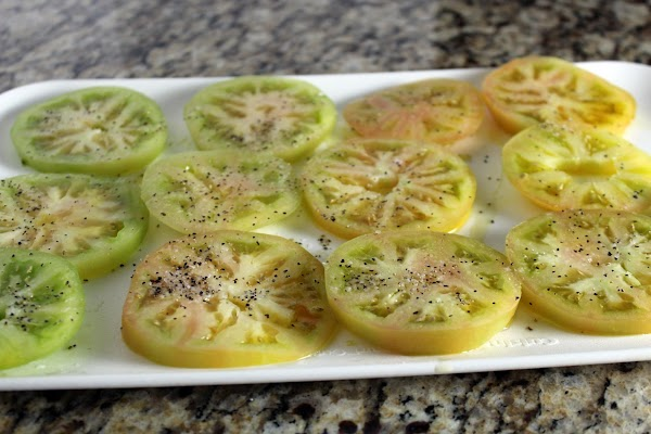 Slice green tomatoes. Rub olive oil, salt, and pepper on tomatoes before placing on...
