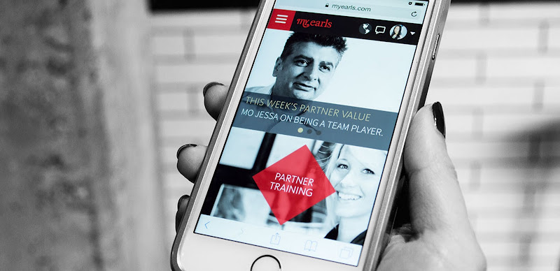 A hand holding up a mobile device with the myEarls intranet website shown on the screen.